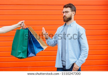 No thanks. rejection refusal and denial. Man putting hands forward pushing stretching hand with paper bags Portrait of a bearded guy on red background.Negation,negative,stop shopping, no sale concep