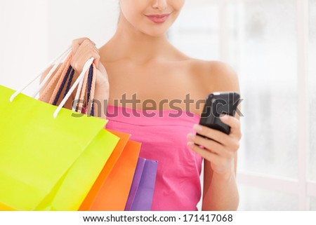 No time for talking. Cropped image of beautiful young woman in pink dress holding shopping bags and mobile phone