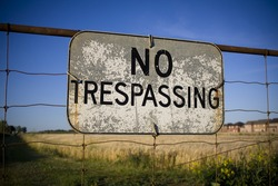 No trespassing sign against backdrop of farmland being encroached by housing development. Urban sprawl concept.