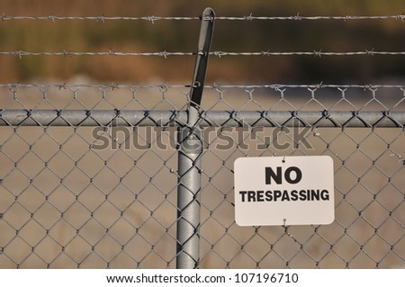 No trespassing sign hanging on a menacing barbed wire fence
