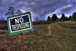 NO TRESPASSING sign in front grass rural country driveway field