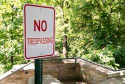 No Trespassing sign posted next to staircase leading down into private property area. Summer time greenery during day time. Signage marking illegal barrier not allowed to pass