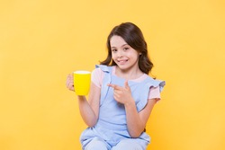 No use crying over spilt milk. Drink enough water. Girl kid hold mug yellow background. Carefree smiling child pointing at mug. Drinking tea juice cocoa. Relaxing with drink. Child drink beverage