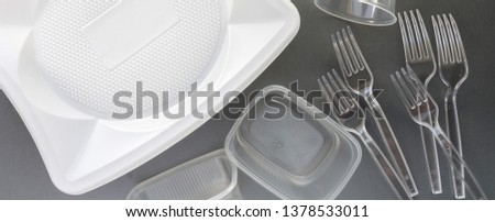 No use symbol in red forbidden sign with plastic dishes around disposable paper dishes and a wooden fork and knife on gray background. Environmental concept. Ban single use plastic. #1378533011