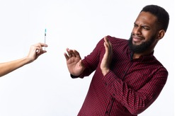 No Vaccination. Scared African Man Gesturing Stop To Hand Offering Syringe With Vaccine Refusing To Be Vaccinated Standing Over White Studio Background. Needle Fobia, Fear Of Covid-19 Vaccines