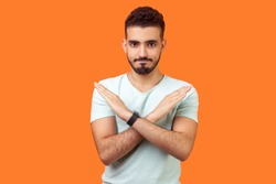 No way, absolutely not. Portrait of determined brunette man with beard in white t-shirt showing x sign with crossed hands, meaning stop, this is the end. studio shot isolated on orange background