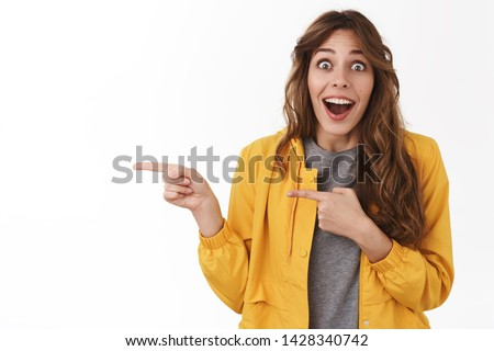 No way awesome. Impressed surprised excited attractive silly girl drop jaw smiling amazed toothy popping eyes thrilled look camera pointing left index finger see incredible good promo sale