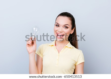 No way! Check it out! Shocked young cute girl is very excited and with open mouth, standing on pure light background with a balb in her hand