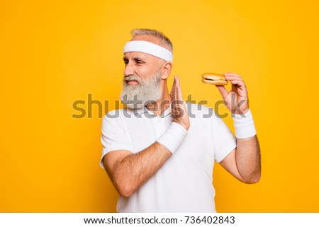 No way! Enough! Serious strict harsh cool athlete holds sandwich, warning with arm, challenge, figure, ban, veto, hunger, interdiction, restrain, refusal, junk food, cheat meal, denial, motivation #736402843