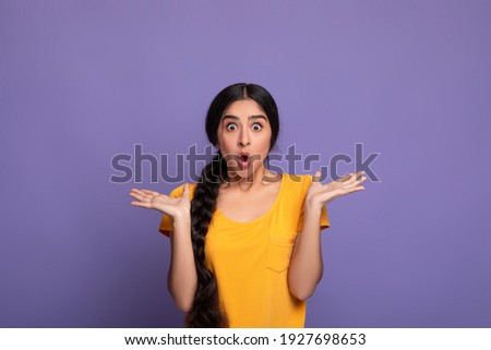 No Way. Portrait of excited surprised and amazed young indian lady looking at camera with open mouth and spreading hands, shocked woman can't believe her eyes, isolated over purple studio background