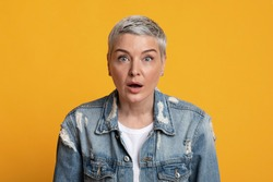 No way. Portrait of shocked middle aged woman opened mouth in amazement, standing over yellow background, free space.