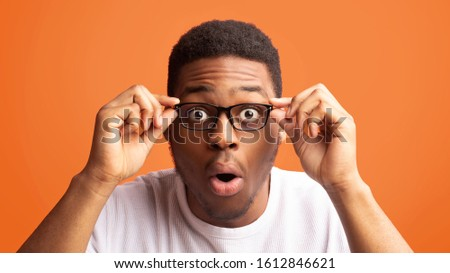 No Way. Shocked black man can't believe his eyes, looking at camera with open mouth, touching glasses, free space