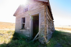 no windows or door on this old weathered abandoned prairie farmhouse with the sunshine peaking over the roof