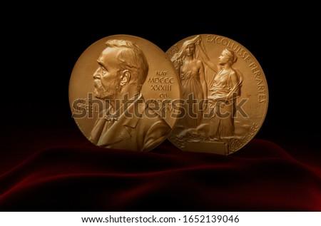 Nobel Prize Medal standing on a platform. Red and black background.