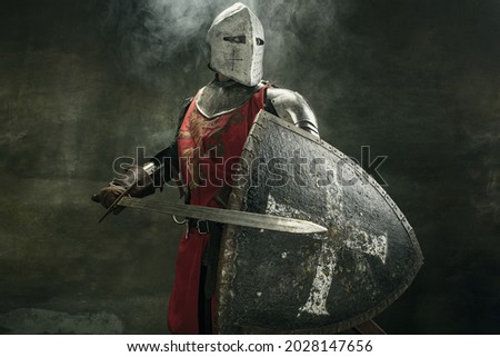 Noble warrior. Portrait of one medeival warrior or knight in armor and helmet with shield and sword posing isolated over dark background.