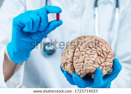 Nocebo Effect Concept. Female doctor holding model of brain and placebo supplement pill, explaining the placebo – nocebo effect phenomenon ストックフォト ©