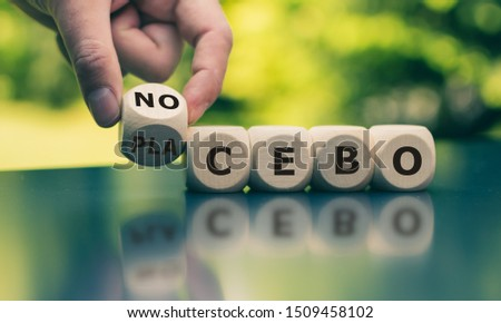 Nocebo or placebo? Hand turns a cube and changes the word 'placebo' to 'nocebo', or vice versa. ストックフォト ©