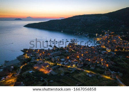 Nocturnal aerial view of seaside town of Komiza on Vis island, Croatia in Dalmatia from drone at night. Tourist destination in the Mediterranean Sea. Small city with street lights in summer at sunset.