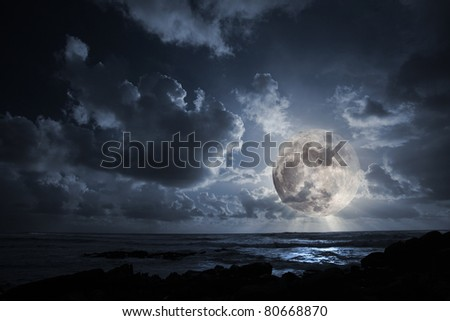 Nocturnal photo composition with moon, clouds, light beams, sea and waves - stock photo