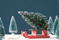 Noel Christmas greeting card with place for text. A bright Christmas tree toy in the form of a fir tree on a Santa Claus sleigh on a dark blue background with toy Christmas trees. Snowing. Front view