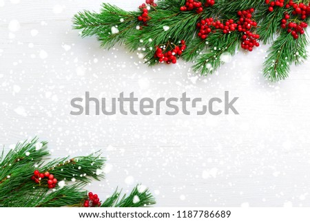 Noel flat lay composition with fir branches and red berries lying on a light wooden background covered with a snow,view from above, blank space for a text #1187786689
