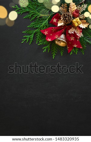 Noel or Christmas greeting card template with copy space for greetings or advertising text, view from above on traditional X-mas decorations lying down moody dark surface with bokeh lights