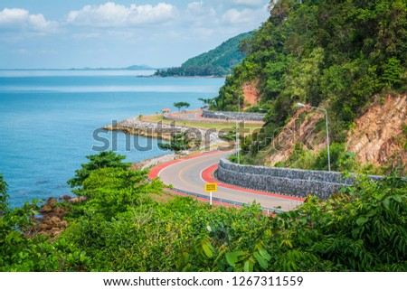 Noen Nangphaya Viewpoint, the famous viewpoint, and landmark of Chanthaburi, Thailand. This viewpoint to see the winding asphalt road with bicycle red road along the coast and mountain with blue sky #1267311559