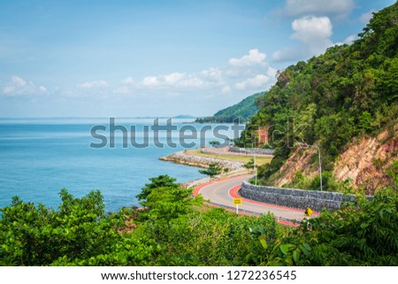 Noen Nangphaya Viewpoint, the famous viewpoint, and landmark of Chanthaburi, Thailand. This viewpoint to see the winding asphalt road with bicycle red road along the coast and mountain with blue sky #1272236545