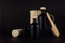 Noir exquisite bathroom decor with blank black cosmetics bottles, bath accessories on dark wood board, mock up. Template for advertising, designers, branding identity, cover.