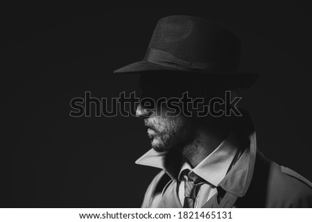Photo of  Noir film detective posing in the dark, thriller and gangsters concept