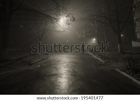 Noir. Silhouette of a passerby on the night street. Black and white
