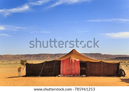 Nomad tents made of camel skin in the middle of the desert with mountains in the background #785961253