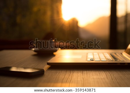 Nomad Work Concept Image Computer Coffee Mug and Telephone on black wood Table and Evening Sunlight shining throw large windows focus on Edge of Laptop