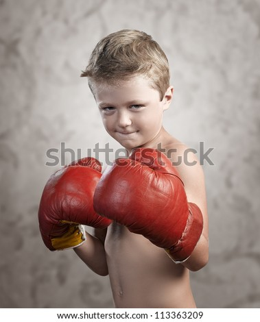 Non Aggressive child wearing boxing gloves on textured background