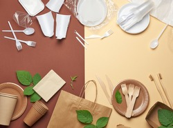 non-degradable plastic waste from disposable tableware and a set of dishes from environmental recycled materials on a brown background. The concept of rejection of plastic, environmental conservation