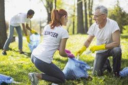 Non profit volunteer. Vigorous two volunteers holding garbage bag and chatting
