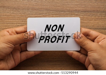 Non Profit written on white card holding with two hands