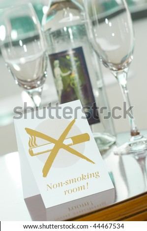 Non-smoking-room label on a desk with glasses and a bottle of mineral water
