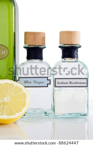 Non-toxic cleaning products from the kitchen cupboard on a shiny reflective surface with white background.  Portrait (vertical) orientation.
