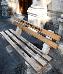 Non whites only -  old bench with an inscription left as  memory of apartheid, racism and segregation.  Non Whites; Only;    street;  Cape Town; Africa