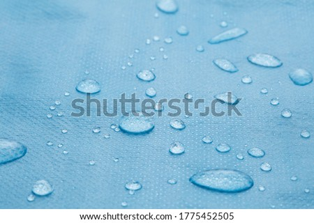 non woven fabric water texture background Water drops on waterproof nylon fabric Macro detail view of texture of blue woven synthetic waterproof clothing Waterproof fabric with water drops Rain Drops Photo stock ©