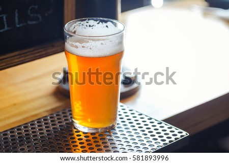 Nonic pint glass full of pale ale standing on a bar counter near draft taps Stock photo ©