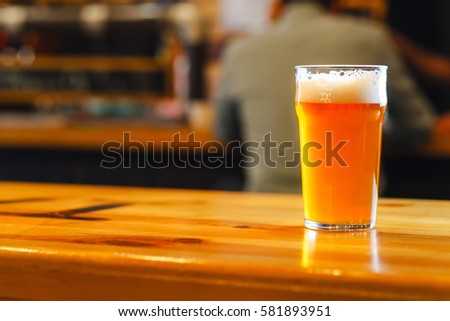 Nonic pint glass with pale ale standing on a wooden table in a pub Stock photo ©