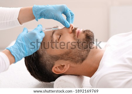 Nonsurgical rhinoplasty concept. Middle-aged bearded businessman visiting aesthetic clinic, getting injection in his nose, side view. Nose filler for handsome man at beauty salon