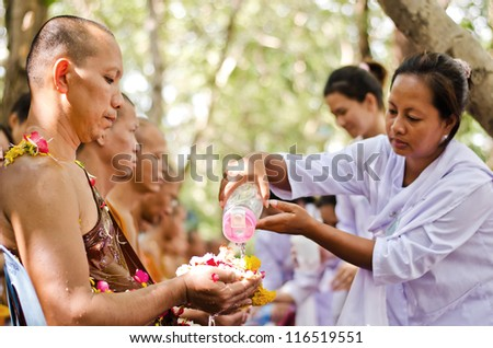 NONTHABURI THAILAND-APRIL13:pe ople celebrate Songkran (new year / water festival: 13 April) by pouring water for buddhist priest and asking for blessings on April 13, 2012 in Nonthaburi,Thailand . - stock photo