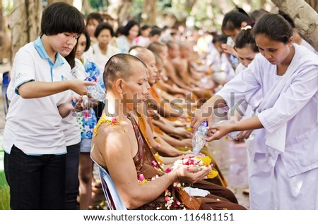 NONTHABURI THAILAND-APRIL13:people celebrate Songkran (new year / water festival: 13 April) by pouring water for buddhist priest and asking for blessings on April 13, 2012 in Nonthaburi,Thailand. - stock photo