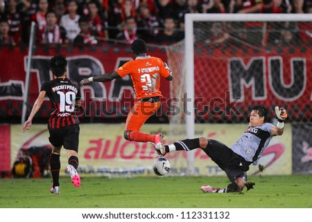 NONTHABURI THAILAND-AUGUST8:Frank Acheampong (no.30 orange)of Buriram utd.in action during Thai Premier League between SCG Muangthong utd.and Buriram utd. on August 8,2012 in Nonthaburi,Thailand