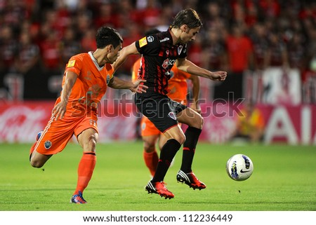 NONTHABURI THAILAND-AUGUST8:Mario Gjurovski (Red) of SCG MuangThong utd. in action during Thai Premier League between SCG Muangthong utd.and Buriram utd. on August 8,2012 in Nonthaburi,Thailand