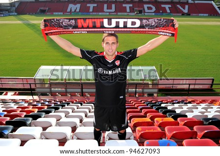 NONTHABURI THAILAND FEBRUARY 08:new player Mario Yurovski of  Muangthong United  holds up a MTUTD Scarf  during  a press conference at Yamaha Stadium on FEBRUARY 8, 2012 NONTHABURI THAILAND