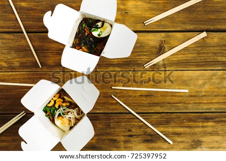 Noodles in box and chopsticks on wooden table background. Flat lay, top view. Chinese takeaway food concept.
